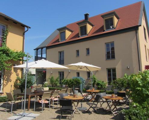 Mediterraner Weinhof mit Holztischen, Stühlen und Sonnenschirmen auf Kiesgrund