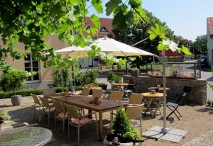 Blick in den sommerlichen Weinhof mit Holztischen, Stühlen und Sonnenschirmen auf Kiesgrund