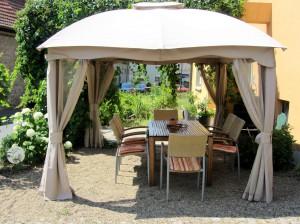 Gruppentisch mit Stühlen und Sitzkissen bequem im Schatten unter einem Pavillon im Weinhof
