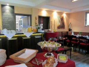Frühstücksraum mit Frühstücksbuffet, Secco und frischer Zopf im Vordergrund, Säfte und Getränke