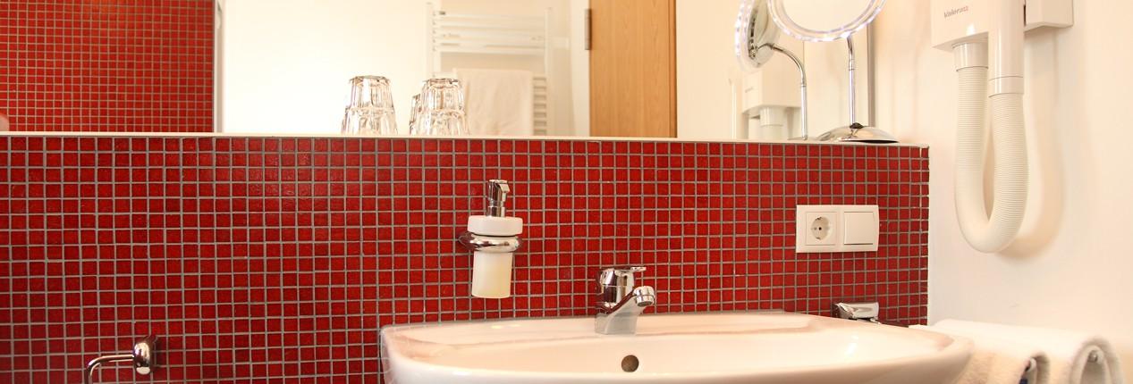 Blick in das helle, rot geflieste Bad mit großem Spiegel