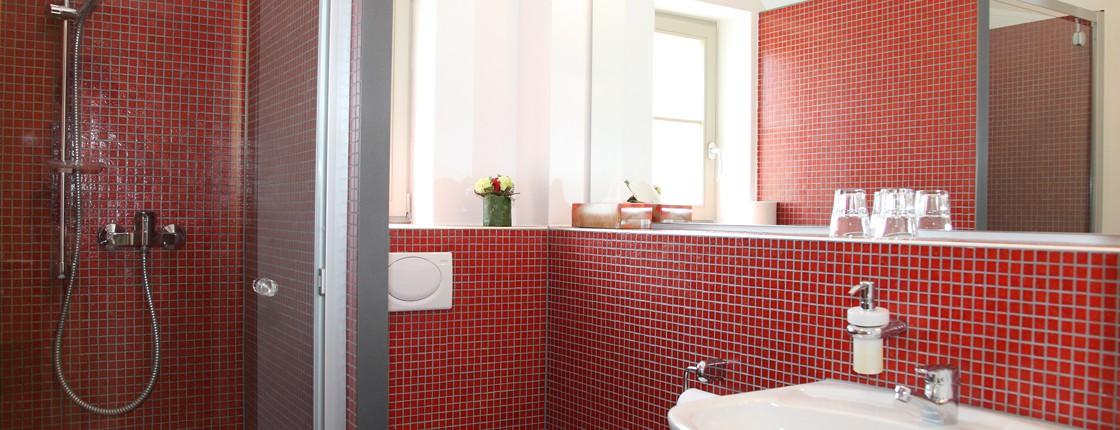 Blick in das helle, rot geflieste Bad mit weißem Waschbecken, WC und Dusche.