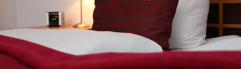 Dichte auf dem Doppelbett mit Blick auf ein Nachtkästchen mit Radiowecker