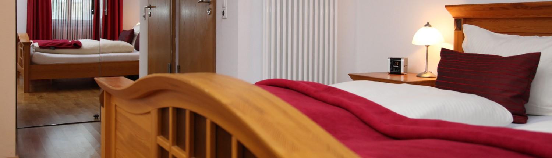Blick quer über das Doppelbett durch ein Doppelzimmer auf den Kleiderschrank