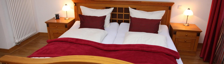 Stilvolles Naturholz-Doppelbett mit weißer und weinroter Bettwäsche